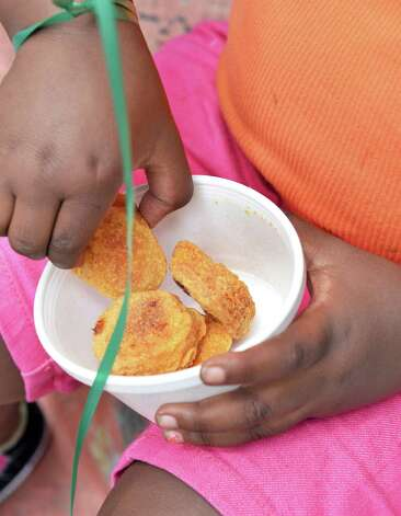 A little girl enjoys chicken nuggets as part of Capital Area Council of Churches' Mobile lunch program on Judson Street Thursday July 23, 2015 in Albany, NY.  (John Carl D'Annibale / Times Union) Photo: John Carl D'Annibale / 00032723A