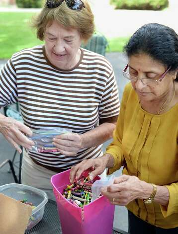 Capital Area Council of Churches volunteers Alice Torda, left, and Raji Bala package donated crayons to include with their Mobile lunch program at First Lutheran Church Thursday July 23, 2015 in Albany, NY.  (John Carl D'Annibale / Times Union) Photo: John Carl D'Annibale / 00032723A