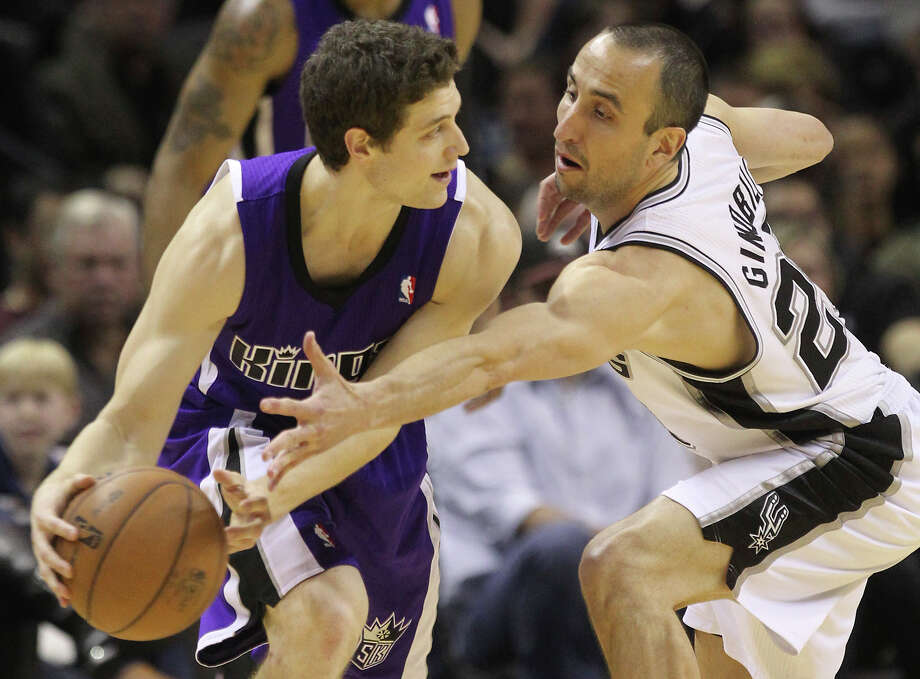 Spurs' Manu Ginobili (20) reaches to attempt a steal against Sacramento Kings' Jimmer Fredette (07) in the second half at the AT&T Center on Friday, Mar. 1, 2013. Spurs defeated the Kings, 130-102. Photo: Kin Man Hui, Staff / San Antonio Express-News / © 2012 San Antonio Express-News