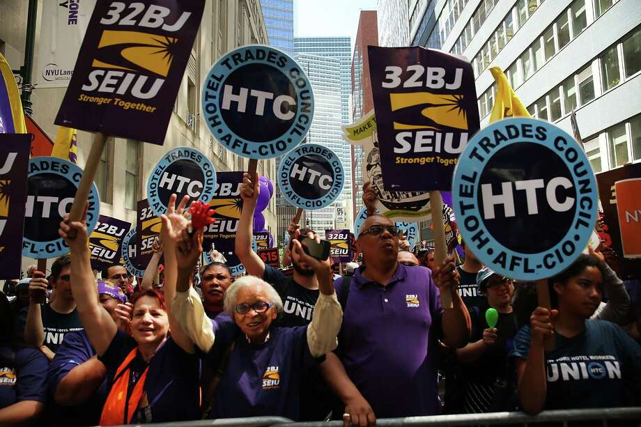 Labor leaders, workers and activists attend a rally for a $15 minimum hourly wage Wednesday in New York City. A panel recommended that the $15 rate be phased in by December 31, 2018, for New York City and by July 1, 2021, for the rest of the state. Photo: Spencer Platt /Getty Images / 2015 Getty Images