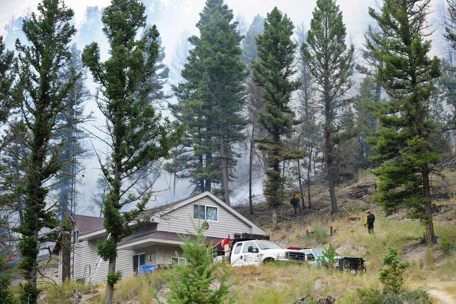 Firefighters fight a flare-up near a residence outside of Townsend, Mont. More than 6 square miles along Glacier National Park's eastern side has burned Photo: Thom Bridge /Associated Press / The Independent Record