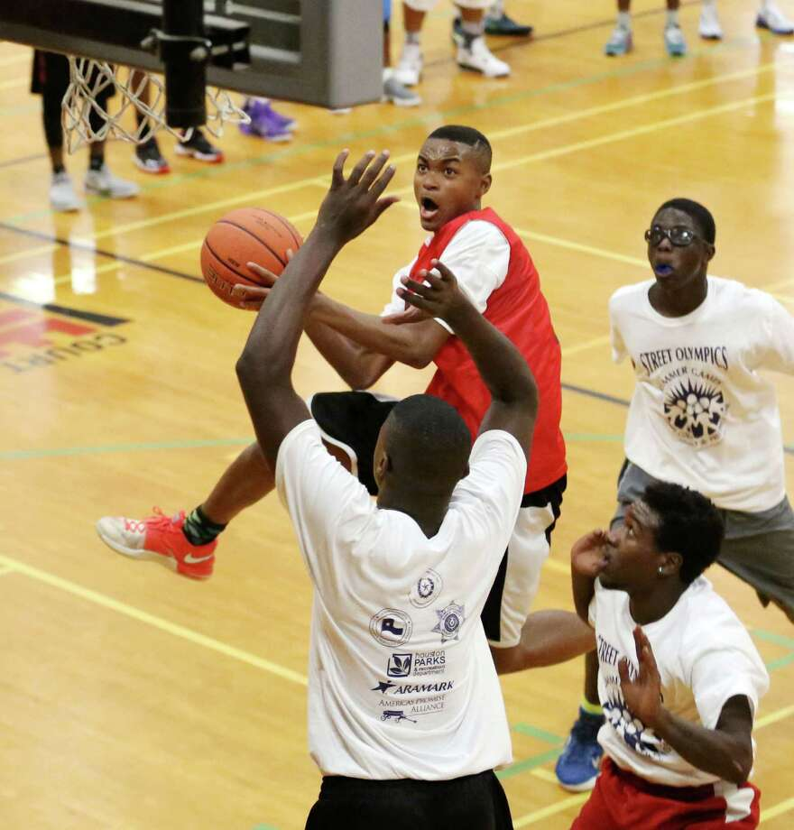 Julian Kegler goes for a layup against Darius Stevens and Albert Nicholson as Deondre Haynes watches from behind Thursday, July 23, 2015, in Houston. The games took place as part of Harris County's 20th Annual Street Olympics 3-on-3 Basketball Championship. Photo: Jon Shapley, Houston Chronicle / © 2015 Houston Chronicle
