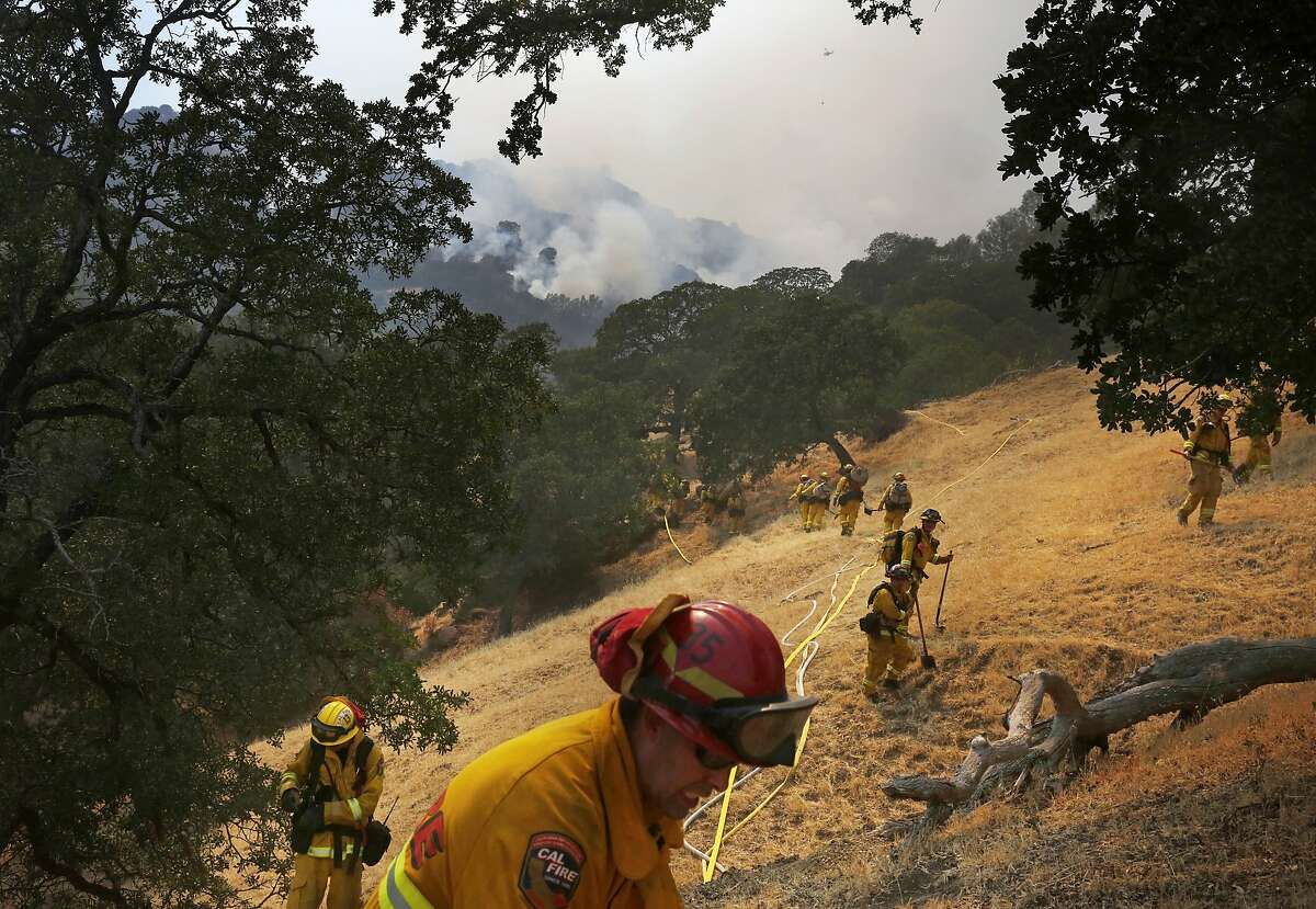 Firefighters hike into a small burning canyon during the Wragg fire that started near Lake Berryessa along hwy 128 July 23, 2015 in Pleasants Valley, Calif.