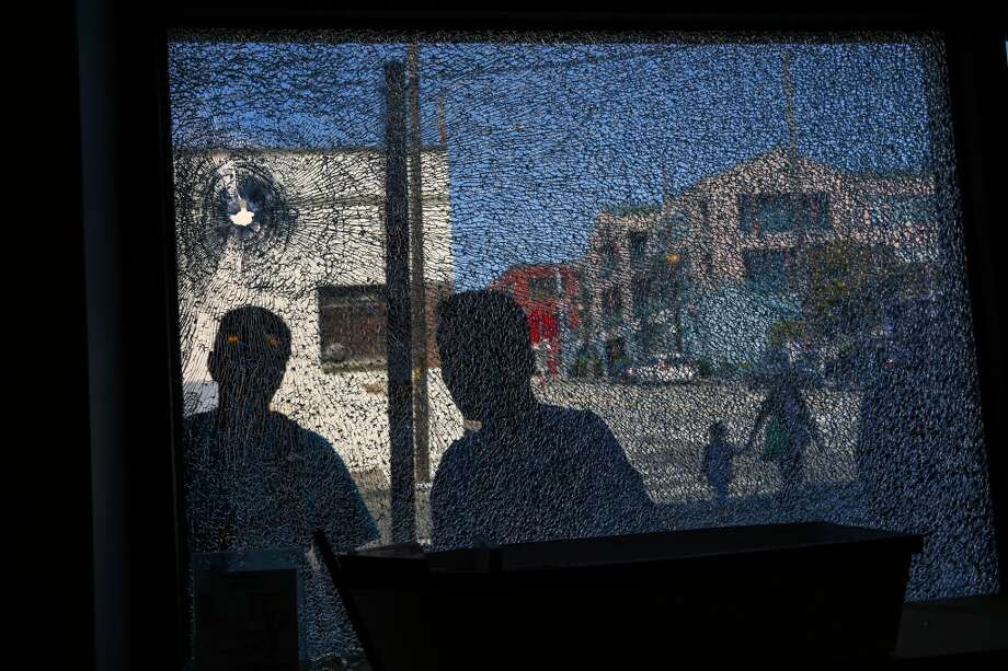 People look at a shattered window at Crawfish King restaurant near the scene where Donnie Chin, the head of the Chinatown-ID Emergency Center, was shot and killed on Thursday, July 23, 2015. Photo: JOSHUA TRUJILLO, SEATTLEPI.COM
