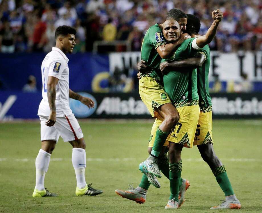 Jamaica's Rudolph Austin, facing camera, celebrates with teammates Joel McAnuff, left, and Je-Vaughn Watson, right, as United States' DeAndre Yedlin walks off the pitch after Jamaica defeated the United States 2-1 in a CONCACAF Gold Cup soccer semifinal Wednesday, July 22, 2015, in Atlanta. (AP Photo/David Goldman) ORG XMIT: GADG117 Photo: David Goldman / AP