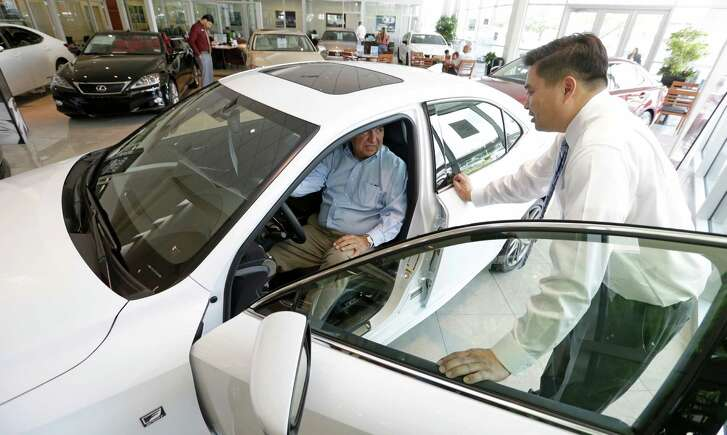Arnold Arevalo, left, of Richmond, looks at a new car with Tony Tran, sales consultant, at Sterling McCall Lexus, 10025 Soutwest Fwy., Thursday, July 23, 2015, in Houston. Group 1 Automotive, Inc., posted its highest quarterly earnings for the three months ending on June 30.