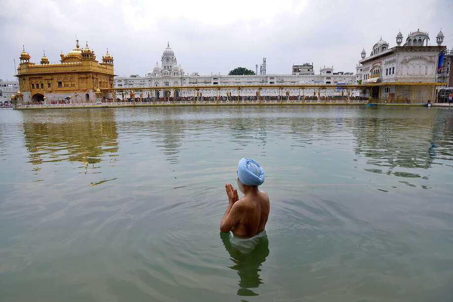 Indian Sikh devotee takes a dip in the holy sarover (water tank ) on the occasion of the birth anniversary of Sikh Guru Harkrishan Sahib at The Golden Temple in Amritsar on July 23, 2015. Guru Har Krishan Sahib Ji, who lived from 1656 to 1664, was the eighth of ten Sikh Gurus. Photo: Narinder Nanu, AFP / Getty Images