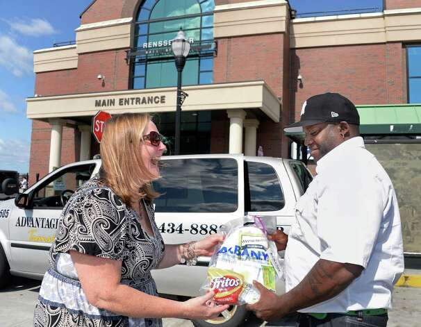 Albany Convention and Visitors Bureau's Gina Mintzer, left, presents a gift bag to Advantage cab driver Chermain Richardson at the Rensselaer train station as part of the bureau's sixth annual Taxi Day Thursday July 23, 2015 in Rensselaer, NY.  (John Carl D'Annibale / Times Union) Photo: John Carl D'Annibale / 00032726A