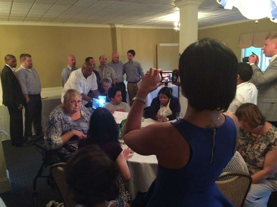 Indiann Harden, whose husband, David, is running for the 4th District Town Council seat in Stratford, Connecticut, gets a picture on her cell phone of all of the Democratic Town Council candidates at the Democratic Town Committee meeting on Wednesday, July 22, 2015. David Harden is at the far left. Photo: John Burgeson / John Burgeson / Connecticut Post