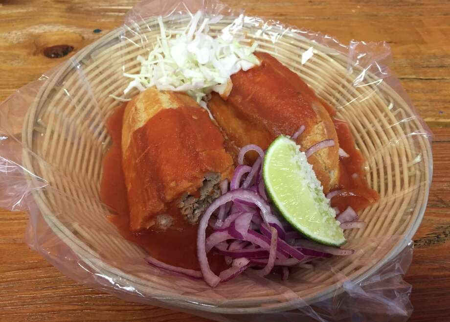 Torta ahogada from Ro-Ho Pork & Bread: A torta ahogada, or drowning sandwich, begins with a crusty sourdough-type bread, filled with carnitas and topped with a mild tomato sauce and pickled onions. Photo: Edmund Tijerina /San Antonio Express-News