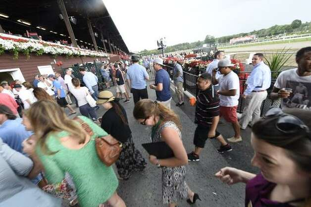 Racing patrons run for cover during a light shower at the Saratoga Race Course on opening day, Friday, July 24, 2015.  Races were delayed for a short time. (Skip Dickstein/Times Union)
