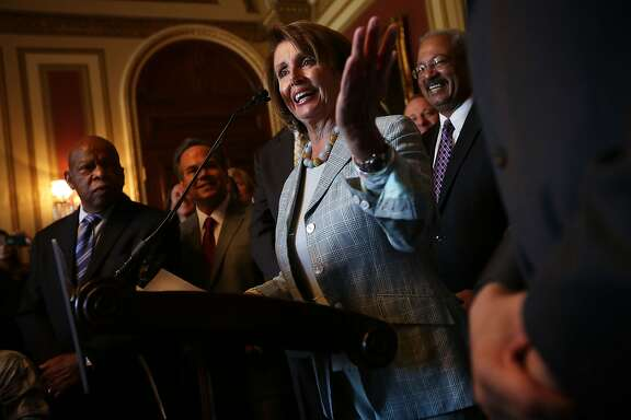 WASHINGTON, DC - JULY 23: Flanked by congressional members, U.S. House Democratic Leader Rep. Nancy Pelosi (D-CA) (C) speaks as Rep. John Lewis (D-GA) (L) listens during a news conference on LGBT discrimination July 23, 2015 on Capitol Hill in Washington, DC. The news conference was to introduce the Equality Act of 2015. (Photo by Alex Wong/Getty Images)