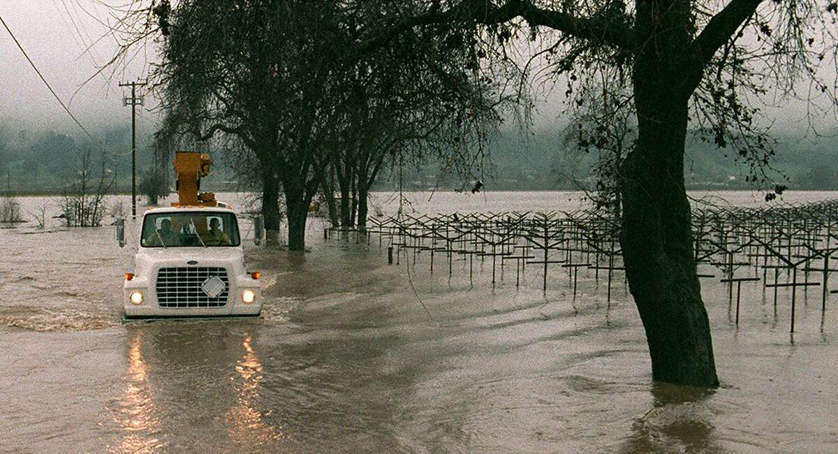 A utility truck in Napa County loses the road while driving past flooded vineyards south of Yountville during major flooding in 1998.