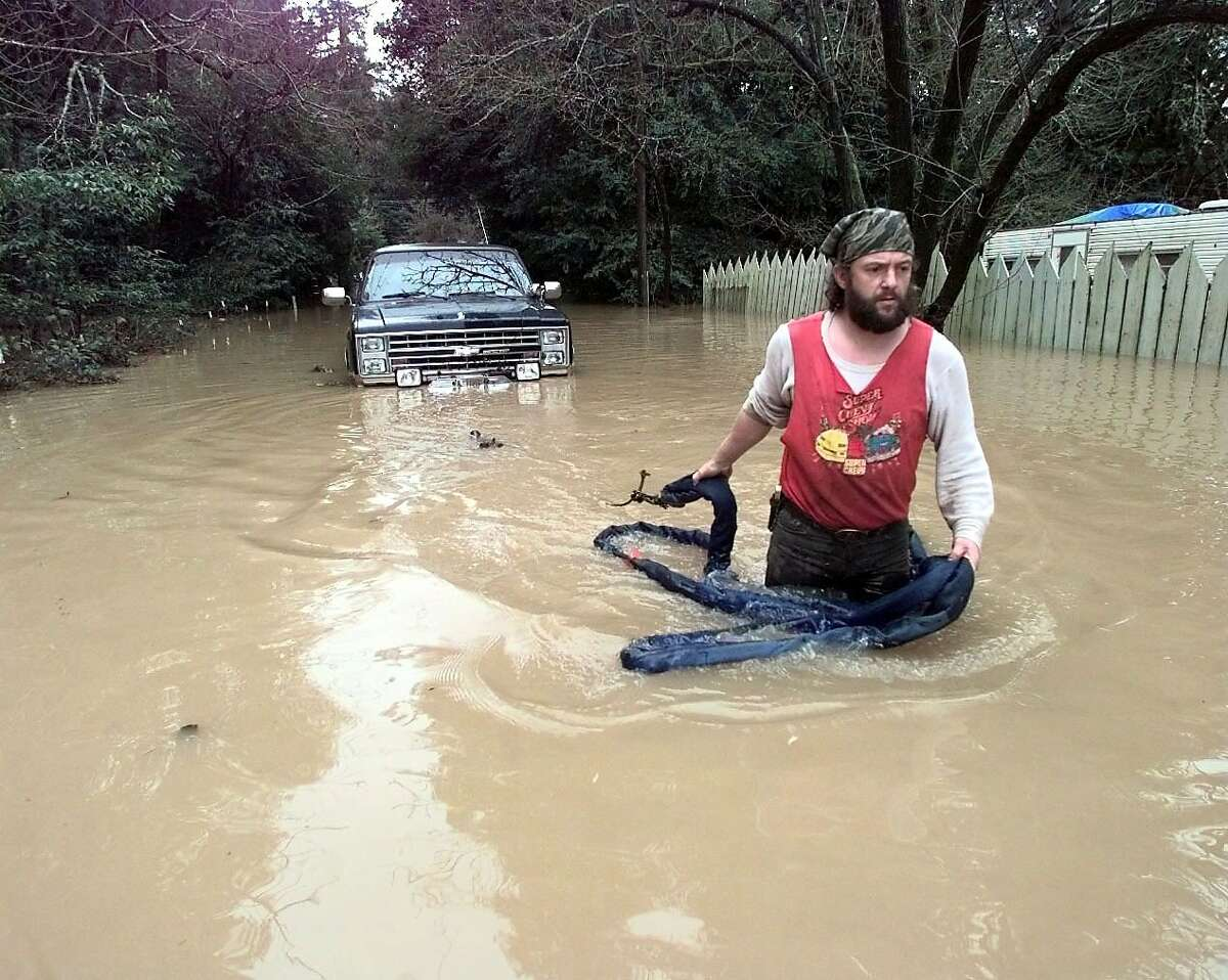Ken Murray wades to shore Feb. 3, 1998, with a winch cable after his friend's truck stalled on flooded Neeley Road in Guerneville. A number of homeowners were trapped behind Russian River floodwaters.