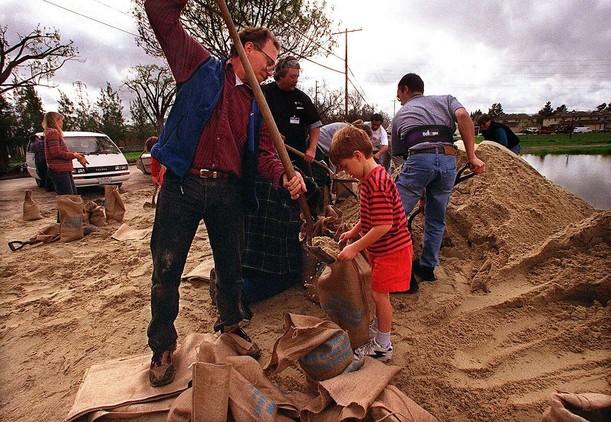 With storm clouds approaching on Feb. 4, 1998, Dan Stober and his son, Andrew, 6, fill sandbags at Greer Park to protect their Palo Alto home.