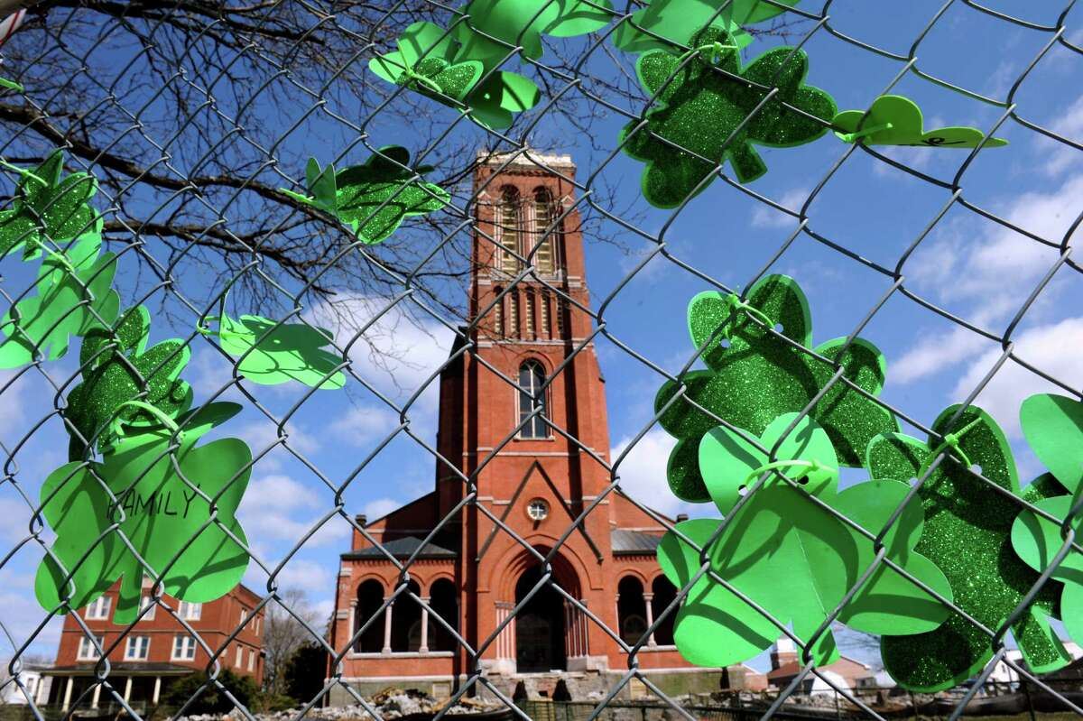 """Cut-out clover leafs, some with works like """"family"""" and """"save,"""" decorate the chain-link fence surrounding Saint Patrick's Church on Wednesday, April 3, 2013, in Watervliet, N.Y. Crews began demolishing the brick shaft way and power house for the church. (Cindy Schultz / Times Union)"""