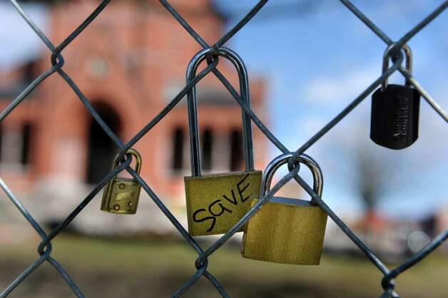 "Locks, one with the word ""save,"" are attached to the chain-link fence surrounding Saint Patrick's Church on Wednesday, April 3, 2013, in Watervliet, N.Y. Crews began demolishing the brick shaft way and power house for the church. (Cindy Schultz / Times Union) Photo: Cindy Schultz / 10021854A"