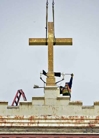 A worker prepares to remove the cross atop the former St. Patrick's church in Watervliet Tuesday Feb. 19, 2013.  (John Carl D'Annibale / Times Union) Photo: John Carl D'Annibale
