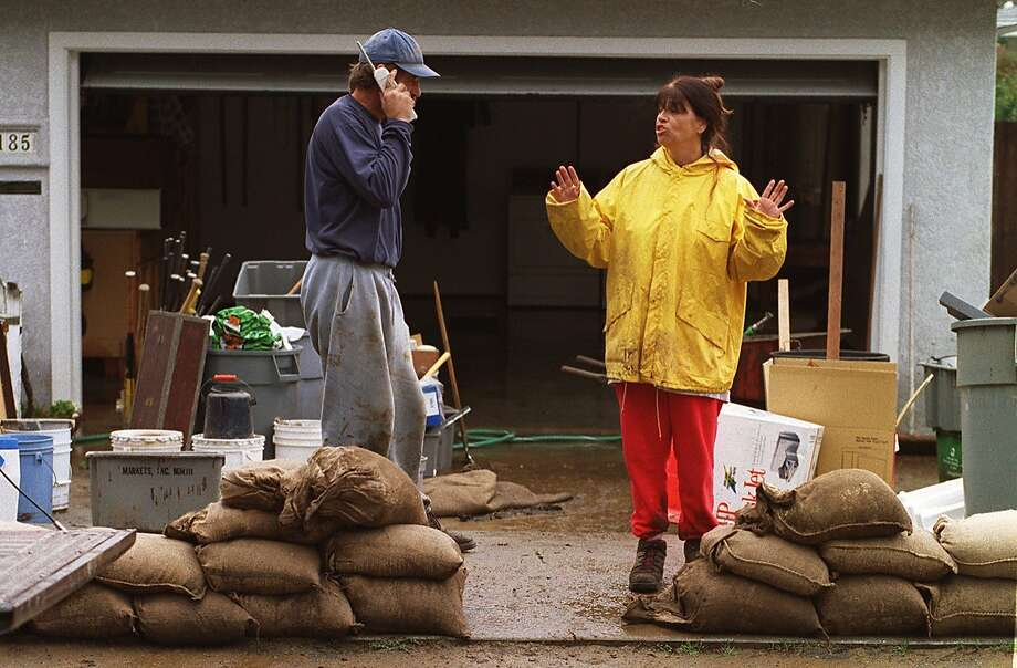 In this February 1998 file photo, Castro Valley residents Bob and Sherry Scott who live along Seaside Av. spent the morning cleaning out their garage of mud which came rushing in earlier in the morning when the small creek near their home overflowed its banks. El Nino can be both godsend and catastrophe. In California, they're counting on it to end one of the most severe droughts in state history. Photo: Michael Macor, The Chronicle