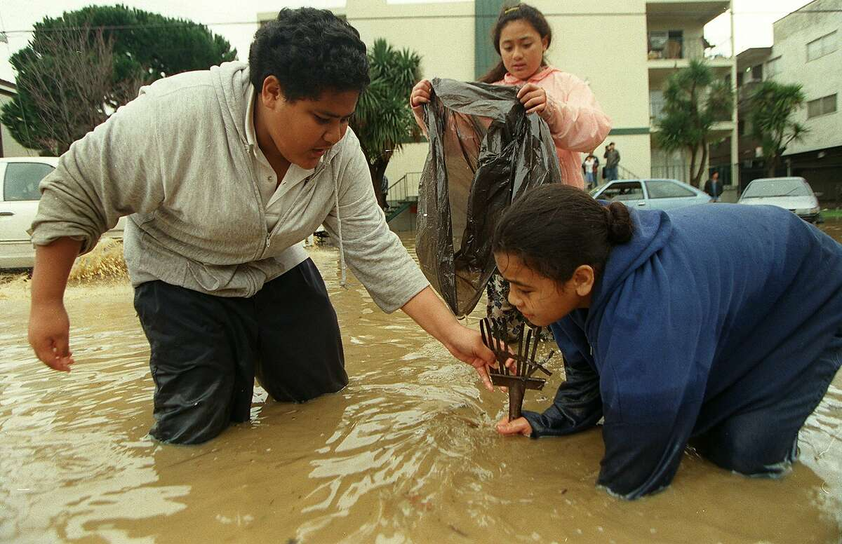 (Left to right) Ofeina Finau, Seilose Finau, (with bag) and Sifa Tangitau try to keep the storm drainage flowing in front of their apartment building on O'Keefe Road in East Palo Alto. The apartments they live in (behind) were invaded by flood in February 1998.