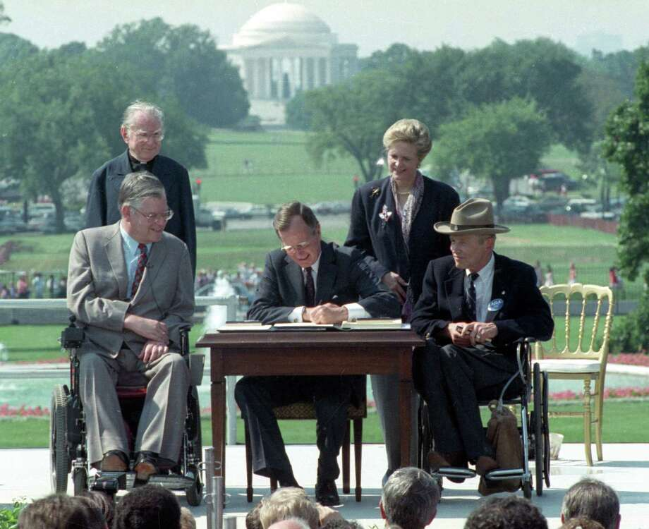 ADVANCE FOR USE SUNDAY, JULY 26, 2014 AND THEREAFTER - FILE - In this July 26, 1990 file photo, President George H. W. Bush signs the Americans with Disabilities Act during a ceremony on the South Lawn of the White House. Joining the president are, from left, Evan Kemp, chairman of the Equal Opportunity Employment Commission; Rev. Harold Wilke; Sandra Parrino, chairman of the National Council on Disability, and Justin Dart, chairman of The President's Council on Disabilities. The Jefferson Memorial is in the background. (AP Photo/Barry Thumma) Photo: Barry Thumma, STF / AP