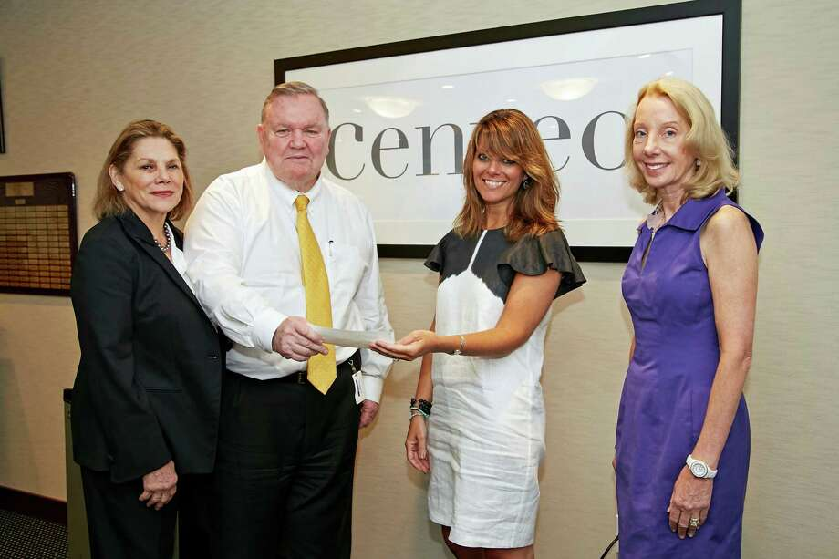 From left, Paula and Robert Burton Sr. hand a check for $50,000 to Breast Cancer Alliance Executive Director Yonni Wattenmaker and President Sharon Phillips. Photo: Contributed / Contributed Photo / Greenwich Time Contributed