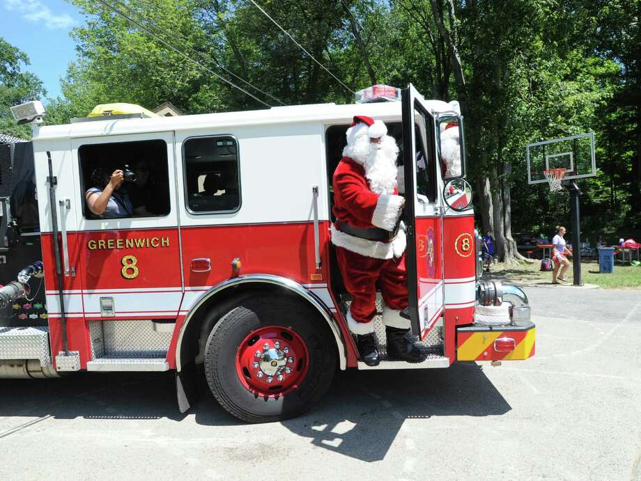 """Santa interacts with campers during the annual """"Christmas in July"""" visit to the Boys & Girls Club of Greenwich at Camp Simmons in Greenwich, Conn., Friday afternoon, July 24, 2015. Photo: Bob Luckey Jr. / Hearst Connecticut Media / Greenwich Time"""