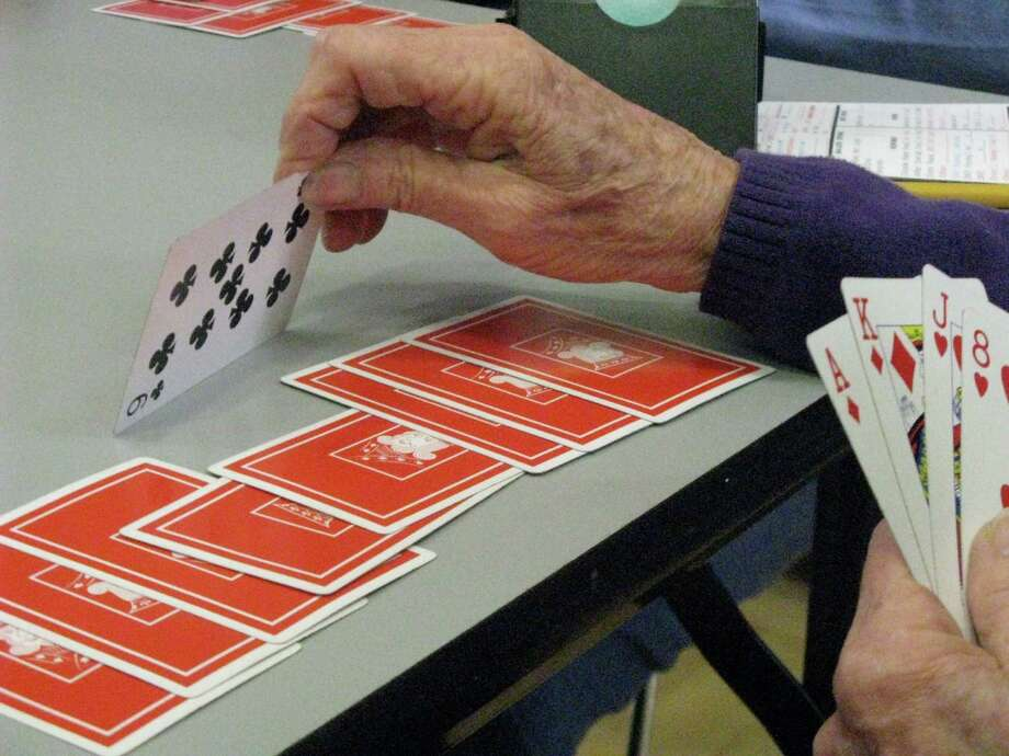 A local bridge buff gets ready to play the nine of clubs duringa Monday duplicate game at the Greenwich YWCA. Photo: Anne W. Semmes / ST / Greenwich Citizen