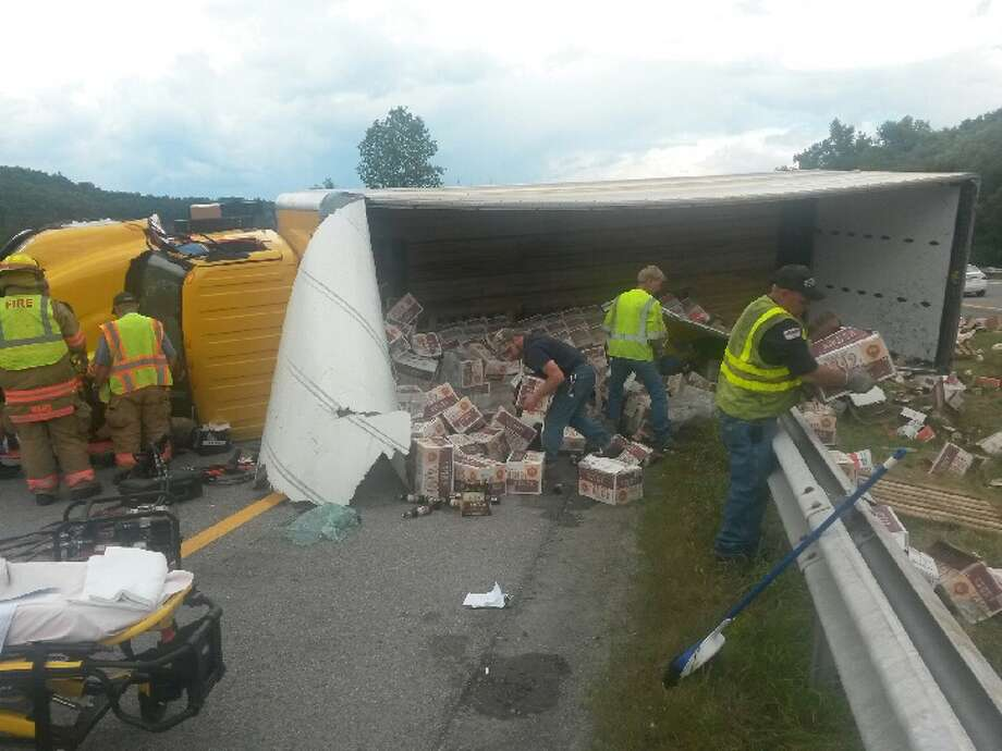 Cleanup crews attend to a tractor-trailer carrying beer that rolled over on the state Thruway Friday afternoon just west of the Fultonville exit in Montgomery County. The driver was taken to Albany Medical Center Hospital with a head and arm injury. (State Police photo)