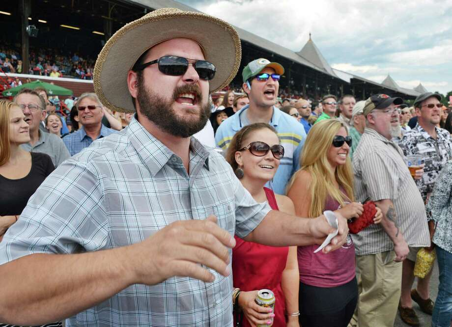 Ryan Skrocki, left, of Adams, Mass., urges on his pick in the first race at Saratoga Race Course Friday July 24, 2015 in Saratoga Springs, NY.  (John Carl D'Annibale / Times Union) Photo: John Carl D'Annibale / 00032586B