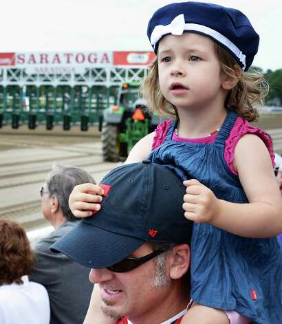 Mathias Molgedey of Springe Germany holds his 2-year-old daughter Mina on his shoulders for a good look at the horses at Saratoga Race Course Friday July 24, 2015 in Saratoga Springs, NY.  (John Carl D'Annibale / Times Union) Photo: John Carl D'Annibale / 00032586B