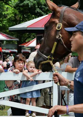 Sharon Jackson and granddaughter Reese Westfall, 3, of Albany watch horses for the first race in the Paddock at Saratoga Race Course Friday July 24, 2015 in Saratoga Springs, NY.  (John Carl D'Annibale / Times Union) Photo: John Carl D'Annibale / 00032586B