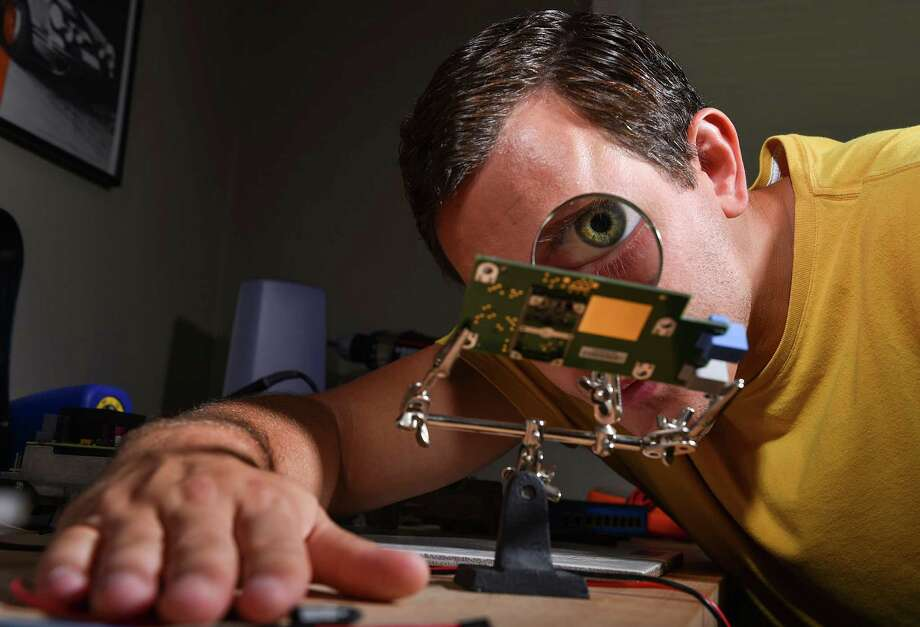 Chris Valasek, director of vehicle security research for IOActive, looks at a telematic board through a magnifying glass last week at his home in Pittsburgh. Valasek is an expert at hacking into engine control modules on automobiles, giving him access to operate certain functions of that automobile from a remote location. Photo: Ricky Carioti /Washington Post / THE WASHINGTON POST
