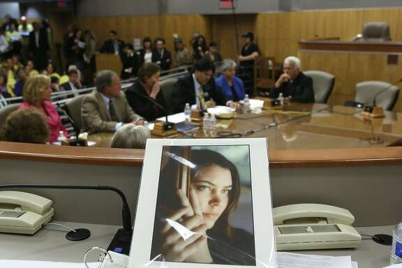 FILE - In this March 25, 2015, file photo, a portrait of Brittany Maynard sits on the dias of the Senate Health Committee at the Capitol in Sacramento, Calif., as lawmakers took testimony on proposed legislation allowing doctors to prescribe life ending medication to terminally ill patients. A San Diego Superior Court judge is expected Friday, July 24, 2015, to hear a motion to dismiss a lawsuit against the state a single mom given only months to live and other California right-to-die advocates. Aid-in-dying advocates thought the nationally publicized case of Maynard, the 29-year-old California woman with brain cancer who moved to Oregon to legally end her life last fall, might usher in a wave of state laws allowing doctors to prescribe life-ending medications. (AP Photo/Rich Pedroncelli)