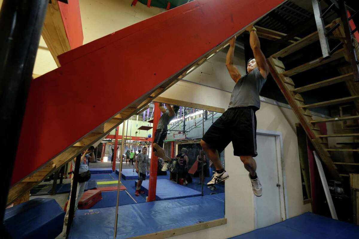 Sam Sann, owner of Iron Sports Fit, climbs the devil steps during his Ninja Training class Tuesday, July 14, 2015, in Houston.