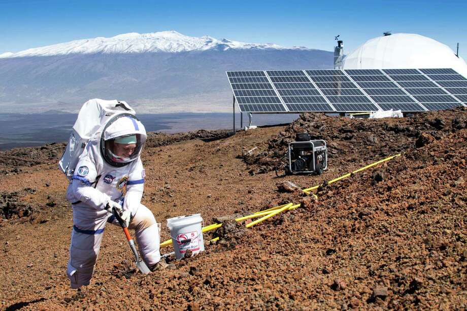 In this March 10, 2015, photo provided by the University of Hawaii at Manoa HI-SEAS Human Factors Performance Study, mission commander Martha Lenio collects a soil sample outside of the dome in which six scientists lived an isolated existence to simulate life on a mission to Mars, on the bleak slopes of dormant volcano Mauna Loa near Hilo on the Big Island of Hawaii. The scientists who took part of a human performance study funded by NASA, stepped outside the dome at 8,000 feet elevation to feel fresh air on their skin Saturday, June 13, 2015, the first time they'd ventured out without donning a space suit in eight months. (Neil Scheibelhut/University of Hawaii at Manoa via AP) MANDATORY CREDIT Photo: Neil Scheibelhut, HONS / University of Hawaii at Manoa