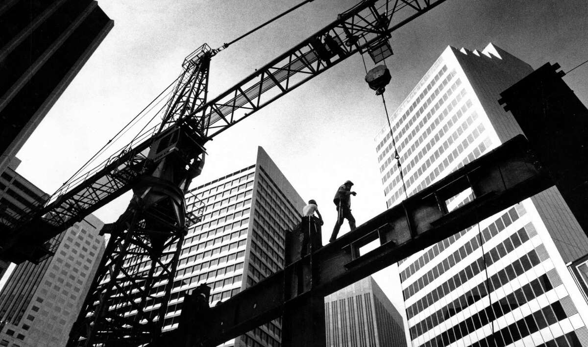 Workers and their equipment lift steel beams to the 11th floor of a building under construction on Market Street in 1985.