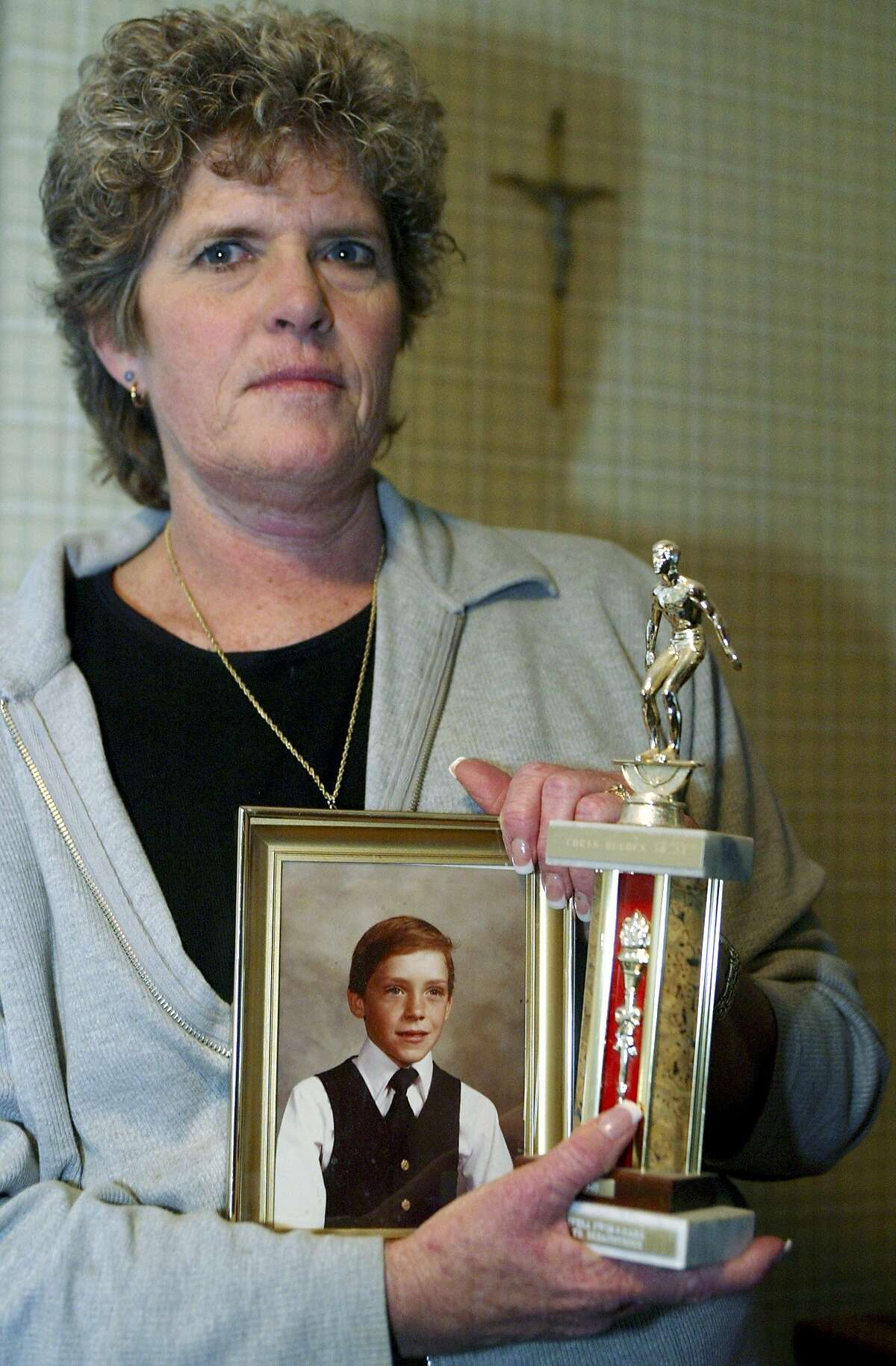 Mary Ann Hughes, poses with a photo of her late son Christopher, then six, Friday Jan.30, 2004, at her home in Chino Hills, Calif. On a June night in 1983, her son Christopher was having a sleepover at the sprawling, hill-top Chino Hills home of Douglas and Peggy Ryen with their two children, Jessica, 10, and Joshua, 8, when they were attacked by someone using a hatchet and a knife. Twenty-one years later, she said she has reserved seats to the convicted killer's execution. And she's keeping her fingers crossed last ditch efforts by celebrities such as Denzel Washington and Mike Farrell to keep Kevin Cooper alive won't get his Feb. 10 execution date postponed.(AP Photo/Damian Dovarganes) Mary Ann Hughes shows a photo of her son, Chris, 6 years old when the picture was taken, at her home in Chino Hills (San Bernardino County). Chris and three others were killed in June 1983.