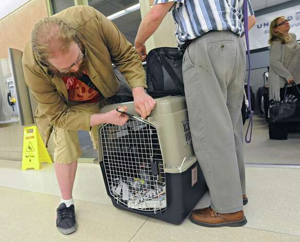 Caleb Sheard of Oregon, left, cuts the plastic ties of his dog Freya's carrier as he and his father Tim Sheard arrive at the Albany International Airport on Thursday, July 24, 2015 in Albany, N.Y. The father, son and dog were traveling to a summer place in upstate New York. (Lori Van Buren / Times Union) Photo: Lori Van Buren / 00032748A