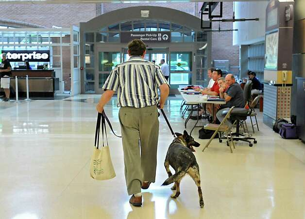 Tim Sheard of Oregon takes Freya the dog out for a walk  after he and his son Caleb Sheard arrive at the Albany International Airport on Thursday, July 24, 2015 in Albany, N.Y. The father, son and dog were traveling to a summer place in upstate New York. (Lori Van Buren / Times Union) Photo: Lori Van Buren / 00032748A