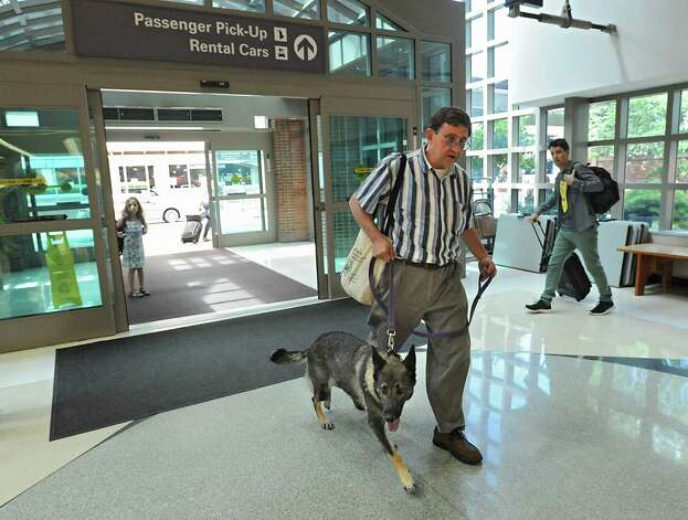 Tim Sheard of Oregon comes back in from taking Freya the dog for a walk after he and his son Caleb Sheard arrive at the Albany International Airport on Thursday, July 24, 2015 in Albany, N.Y. The father, son and dog were traveling to a summer place in upstate New York. (Lori Van Buren / Times Union) Photo: Lori Van Buren / 00032748A