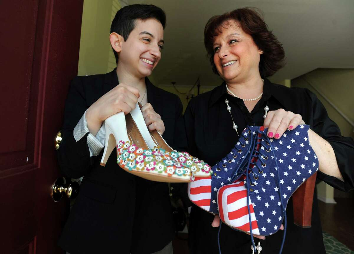 Elizabeth Laudadio and her mom Lisa Gfeller hold up two of her sister Kathryn Laudadio's more than 200 pairs of designer shoes Friday, July 24, 2015, at Gfeller's home in Bridgeport, Conn. Kathryn, who died after a battle with anorexia and bipolar disorder, was a fashionista and her vast collection of shoes is being listed on Fashion Project, a charitable re-commerce platform, with 55 percent of the proceeds going to Project HEAL, a treatment facility for eating disorder sufferers.