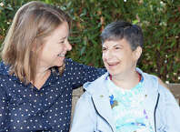 Liz Menten, at left, will be honored for all her work at Pathways at the nonprofitís annual benefit in September. Here she shares some time and a smile with Pathways client Debbie Biagi.