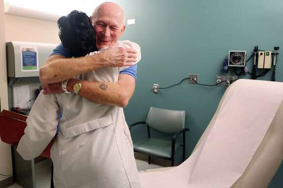 Nurse Beena Varghese greets Bruce Campbell during his appointment at MD Anderson Cancer Center last month. Campbell, who has Stage 4 lung cancer, has been receiving immunotherapy for the last year and a half.  His oncologist, John Heymach, below, proposed the treatment.