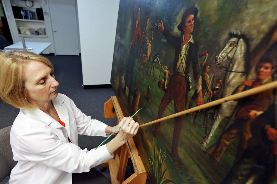 "Anne Zanikos works on Harry Arthur McArdle's painting ""Ben Milam Calling for Volunteers."" Because of its previous poor condition, it hadn't been displayed since 2000. But it may return to the Alamo next month. Photo: Edward A. Ornelas /San Antonio Express-News / © 2015 San Antonio Express-News"