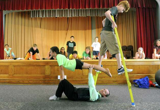 Teacher Seano Fagan, on ground, holds up student Emily Lopez, 10, as Alex Stafford, 14, walks over them on stilts  during the Broadway Bootcamp Circus Arts with Circus Theatricks at The College of Saint Rose on Friday July 24, 2015 in Albany, N.Y. (Michael P. Farrell/Times Union) Photo: Michael P. Farrell / 00032743A