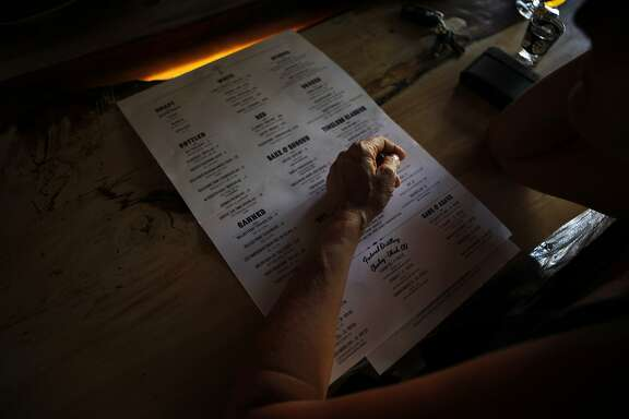 A customer looks at the cocktail menu at Grange Hall.