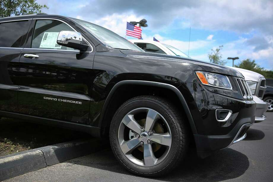 A Fiat Chrysler Jeep Grand Cherokee is seen on a sales lot Friday, the day the company announced it is recalling about 1.4 million Dodges, Jeeps, Rams and Chryslers equipped with certain radios. Photo: Joe Raedle /Getty Images / 2015 Getty Images