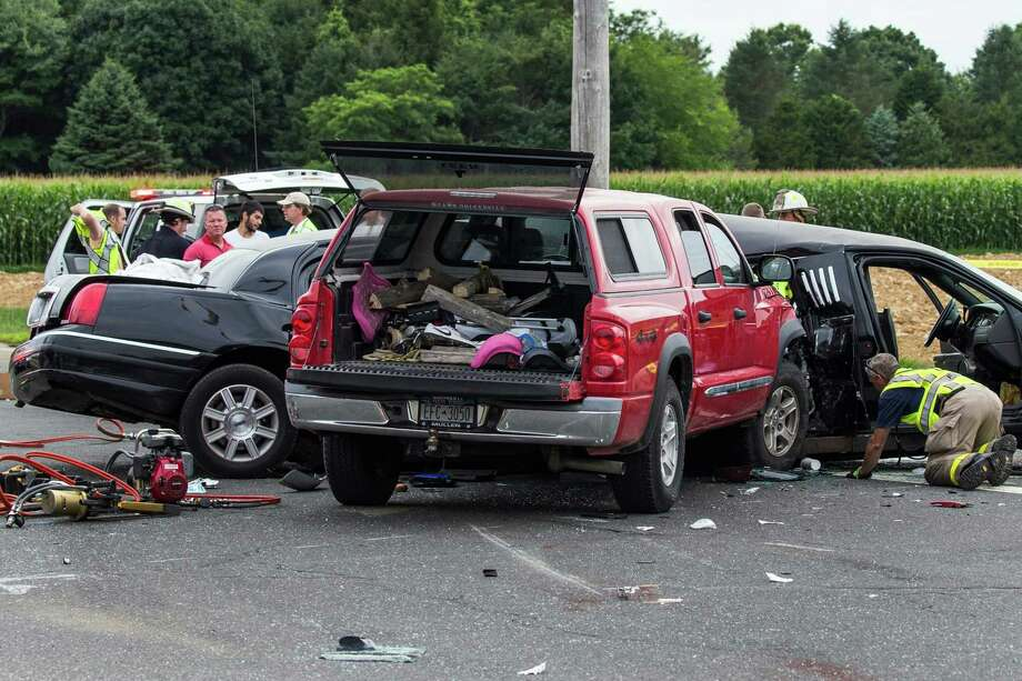 """FILE - This July 18, 2015 file photo shows authorities investigating the scene of a fatal crash between a limousine and sports utility vehicle in Cutchogue, N.Y. A New York prosecutor says a misdemeanor DWI charge remains in effect """"at this time"""" for the pickup truck driver who police say slammed into a limousine in Long Island wine country, leaving four women dead and four others injured.  (Randee Daddona/Newsday via AP, File)  ORG XMIT: NYANE205 Photo: Randee Daddona / Newsday"""