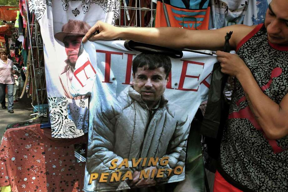 "A vendor in Mexico City holds up a T-shirt for sale that has Joaquin ""El Chapo"" Guzman's face on it. Photo: Alfredo Estrella /Getty Images / AFP"